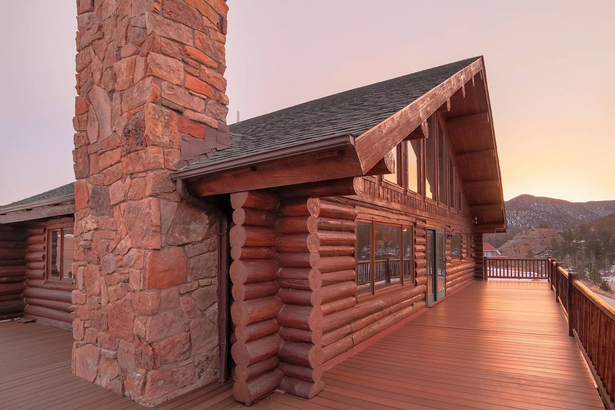 A side view of a log cabin with a peaked roof, large stone fireplace on the left, and a large deck with mountain views.m