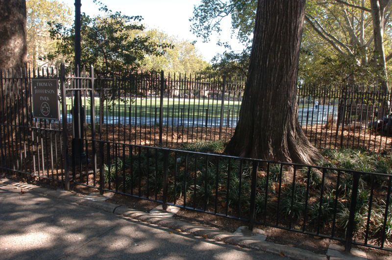 A park with trees and a fence.