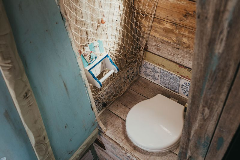 The toilet area of the camper features a white toilet set into a wooden seat, white a blue door to the left and fish net for decor.