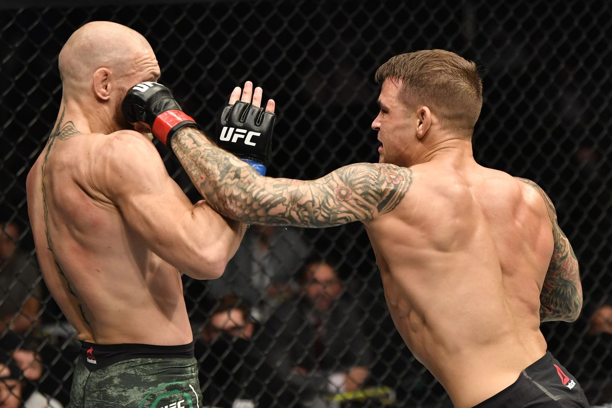 In this handout image provided by the UFC, Dustin Poirier punches Conor McGregor of Ireland in a lightweight fight during the UFC 257 event inside Etihad Arena on UFC Fight Island on January 23, 2021 in Abu Dhabi, United Arab Emirates.