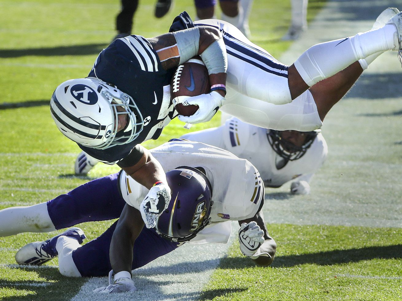 Brigham Young Cougars running back Tyler Allgeier (25) gets flipped into the air by a North Alabama defender as he dives for the end zone during a game in Provo on Saturday, Nov. 21, 2020.