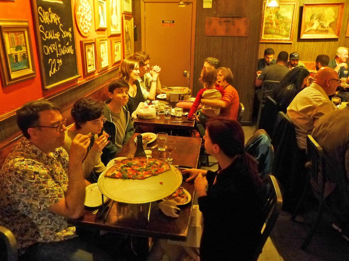 A room crowded with tables, with parts of pizzas scattered around.
