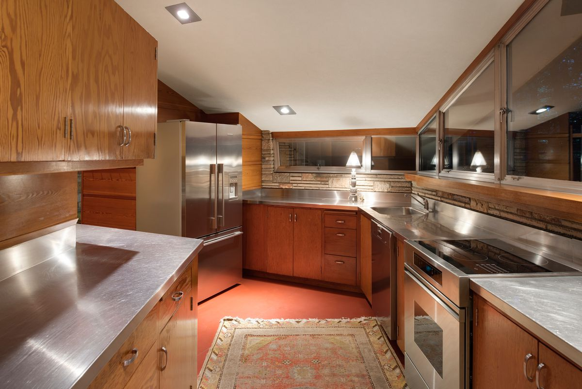 A kitchen has stainless steel counters, wooden cabinets, and red floors.