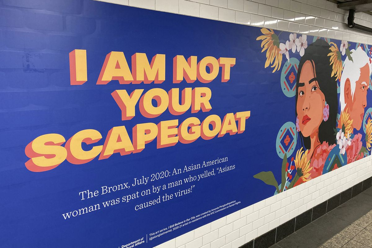 """A billboard in a subway in Brooklyn reads, """"I am not your scapegoat"""" and features an illustration of an Asian woman."""