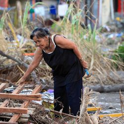A woman searches through debris in Tacloban, Tuesday, Nov. 19, 2013 following a typhoon.