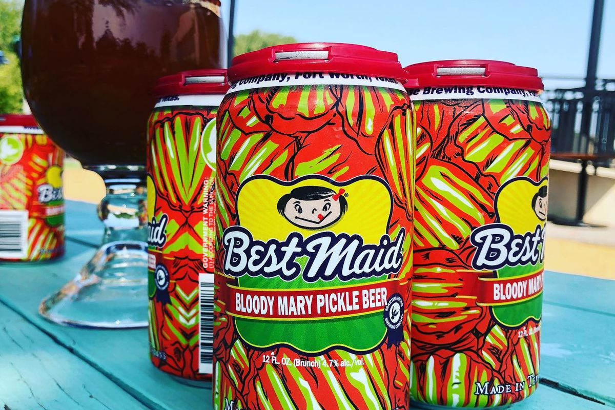 """a four-pack of beers, the cans of which are bright green and red. The name of the beer is """"bloody mary pickle beer."""" They are sitting on a blue-painted picnic table and in the background there is a large mug filled with a dark red liquid."""