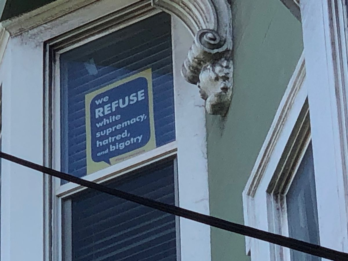 """A sign in a window that reads: """"We refuse white supremacy, hatred. and bigotry."""""""