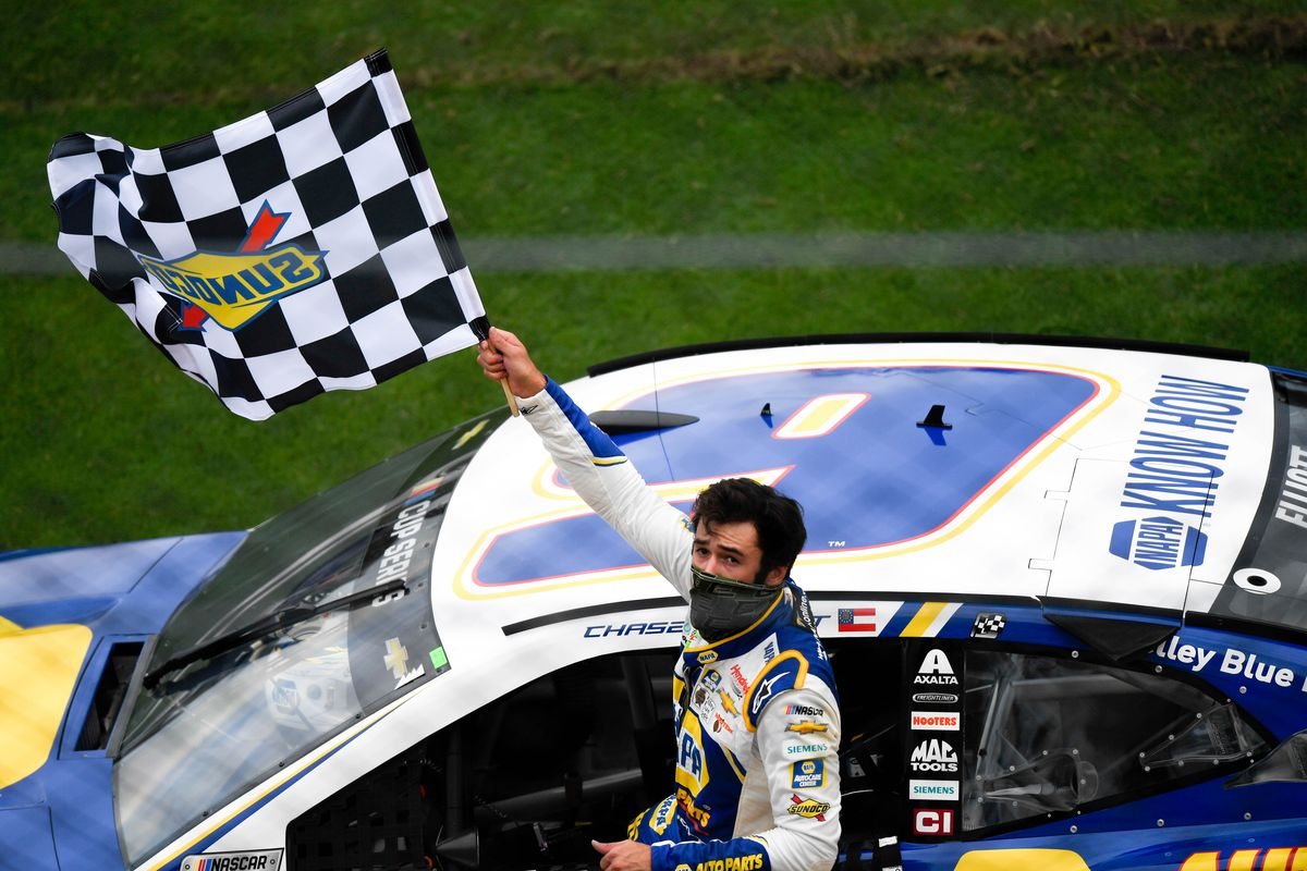 NASCAR Cup Series driver Chase Elliott waves the checkered flag to the fans after winning the Go Bowling 235 Road Course at Daytona International Speedway.