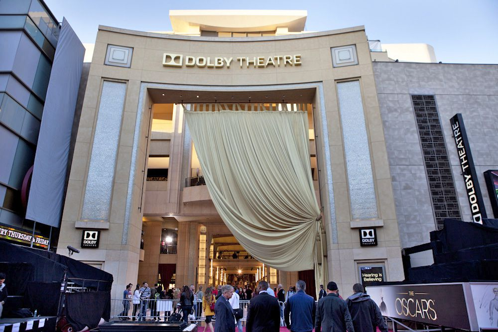 The entrance to a building which has an elaborate entryway with a pulled back curtain. The letters on the building read: Dolby Theatre.