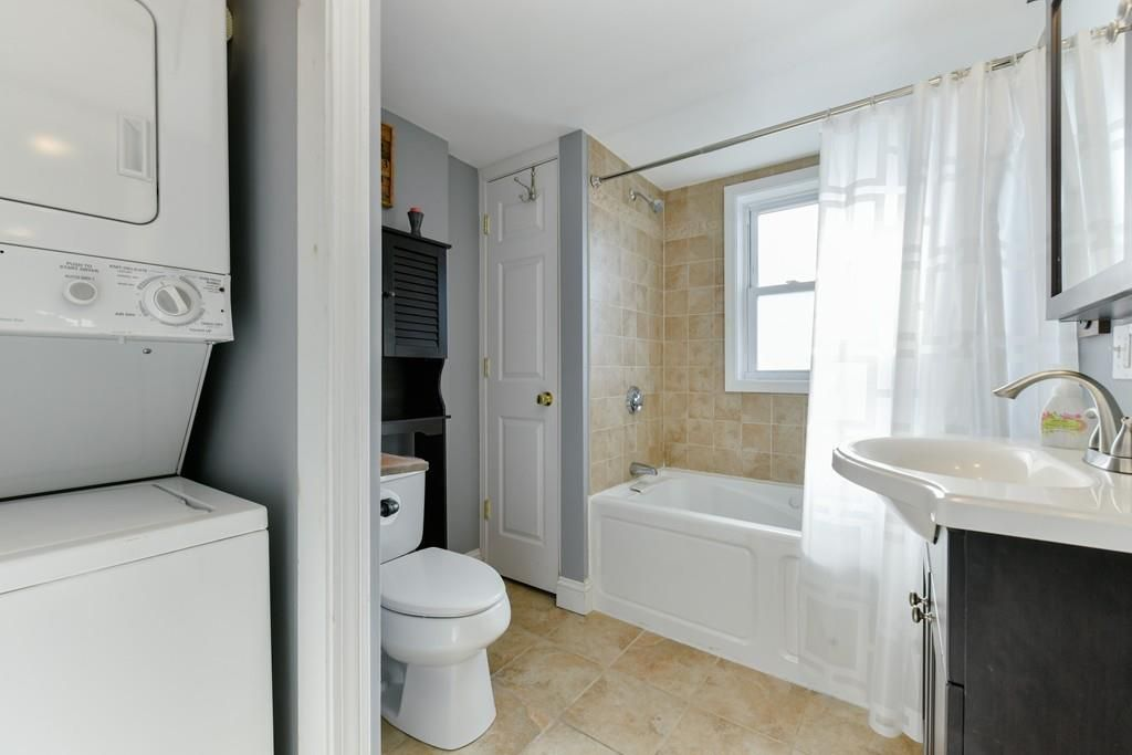 A bathroom with the curtain pulled back on the shower and a stacked washer-dryer in the foreground.