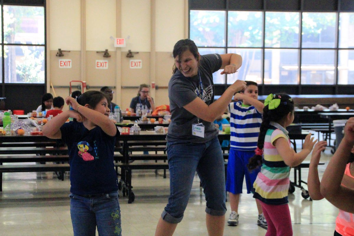 Students and teachers dance together after lunch at a Memphis Teacher Residency Camp held this summer at Kingsbury Elementary School.