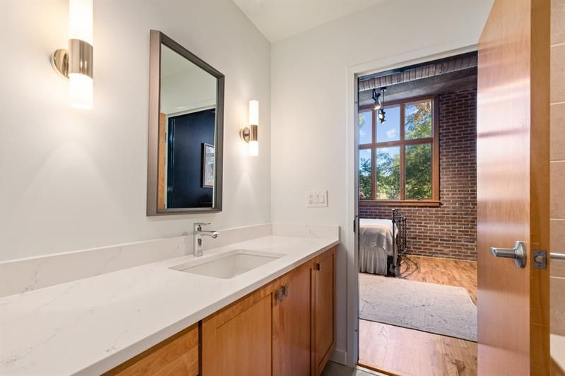 A long white bathroom with a  wooden door.