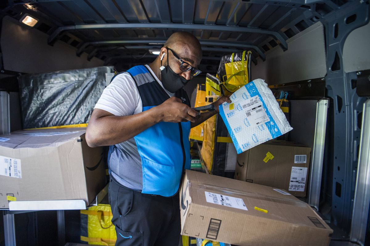 An Amazon delivery driver scans packages inside a van.