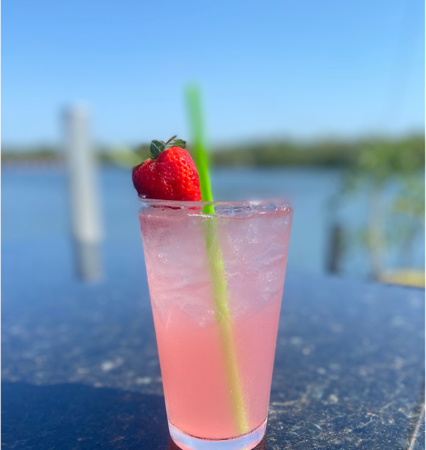 A pink cocktail with a whole strawberry on the rim with a green straw and a view of the water