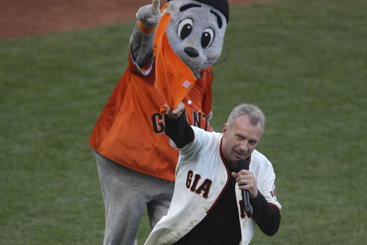 """Former San Francisco 49ers quarterback Joe Montana leads a """"Go Giants"""" chant with San Francisco Giants team mascot Lou Seal before Game 5 of the National League baseball championship series against the St. Louis Cardinals at AT&T Park in San Francisco, Ca"""
