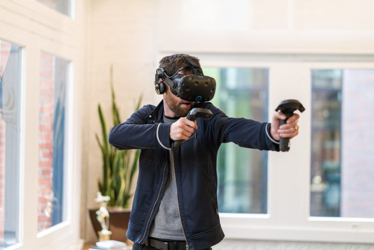 man wearing HTC Vive headset and holding Vive wand controllers