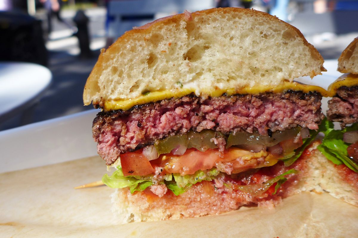A burger cut in cross section to show pink juicy meat and toppings above and below inside the bun.