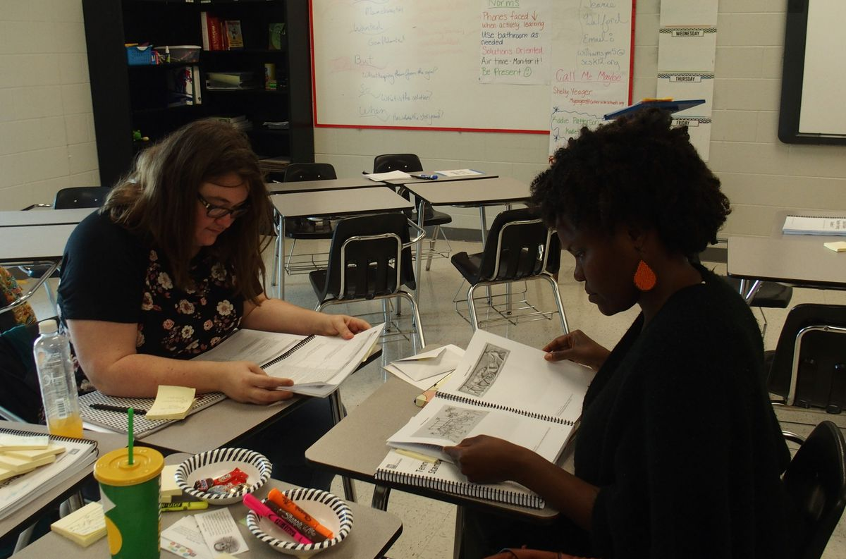 Middle school social studies teachers Zan Brennan and Chloe Smuk discuss the new state standards during their lunch break at a teacher training held in June at Arlington High School.