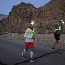 hor Kim Law (L) of China ascends Whitney Portal Road to the finish of the AdventurCORPS Badwater 135