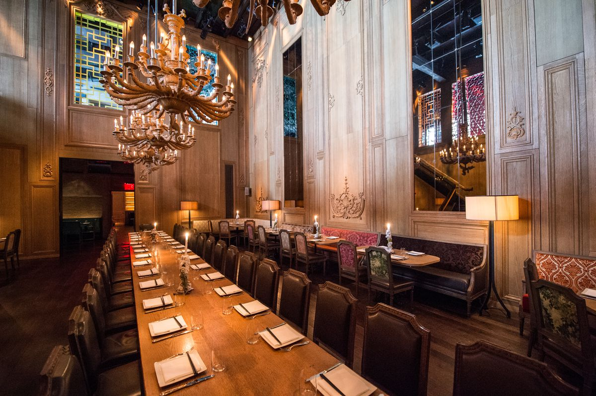 An ornate, high-ceilinged dining room with a chandelier and long communal table set for service