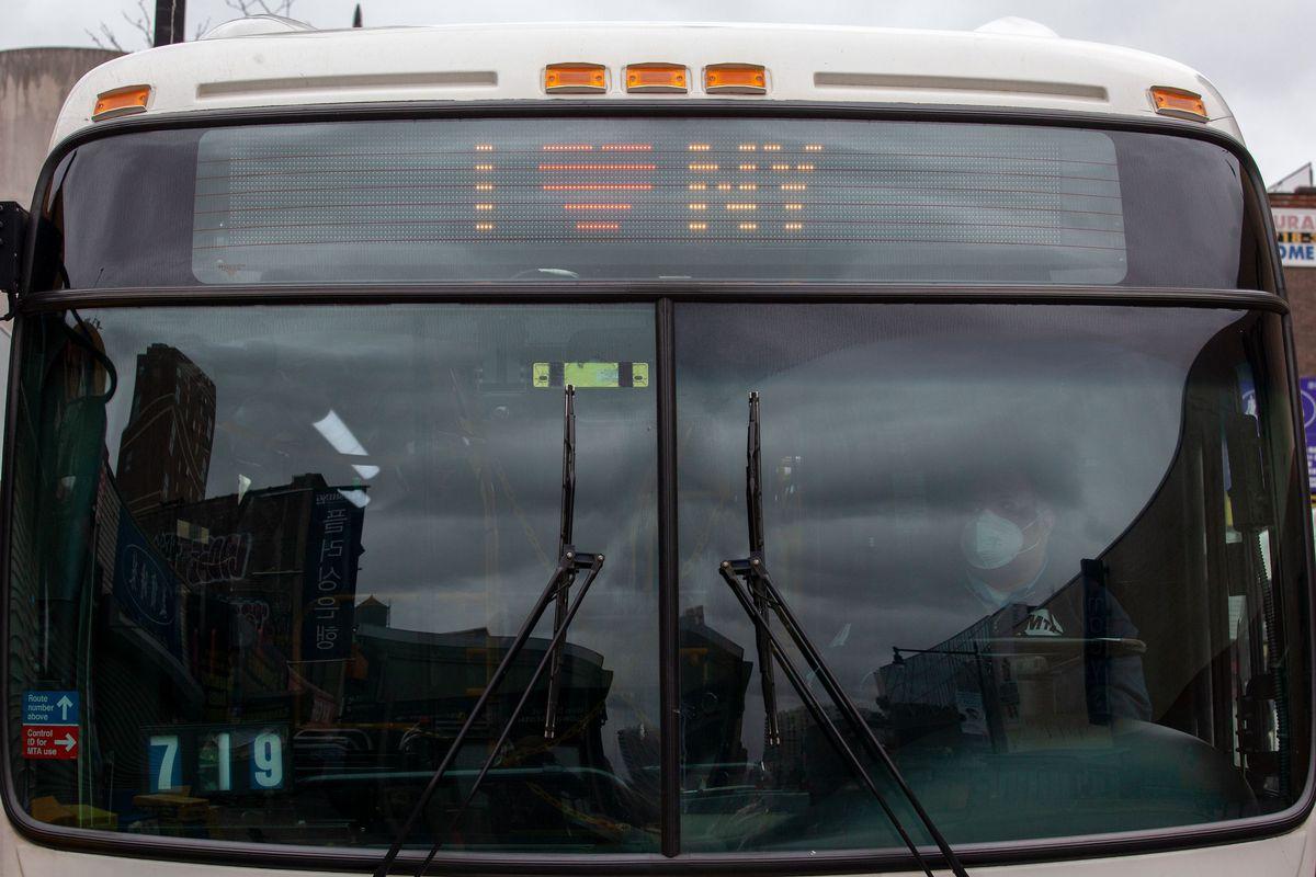 An MTA worker drives a bus through Flushing, Queens during the coronavirus outbreak.