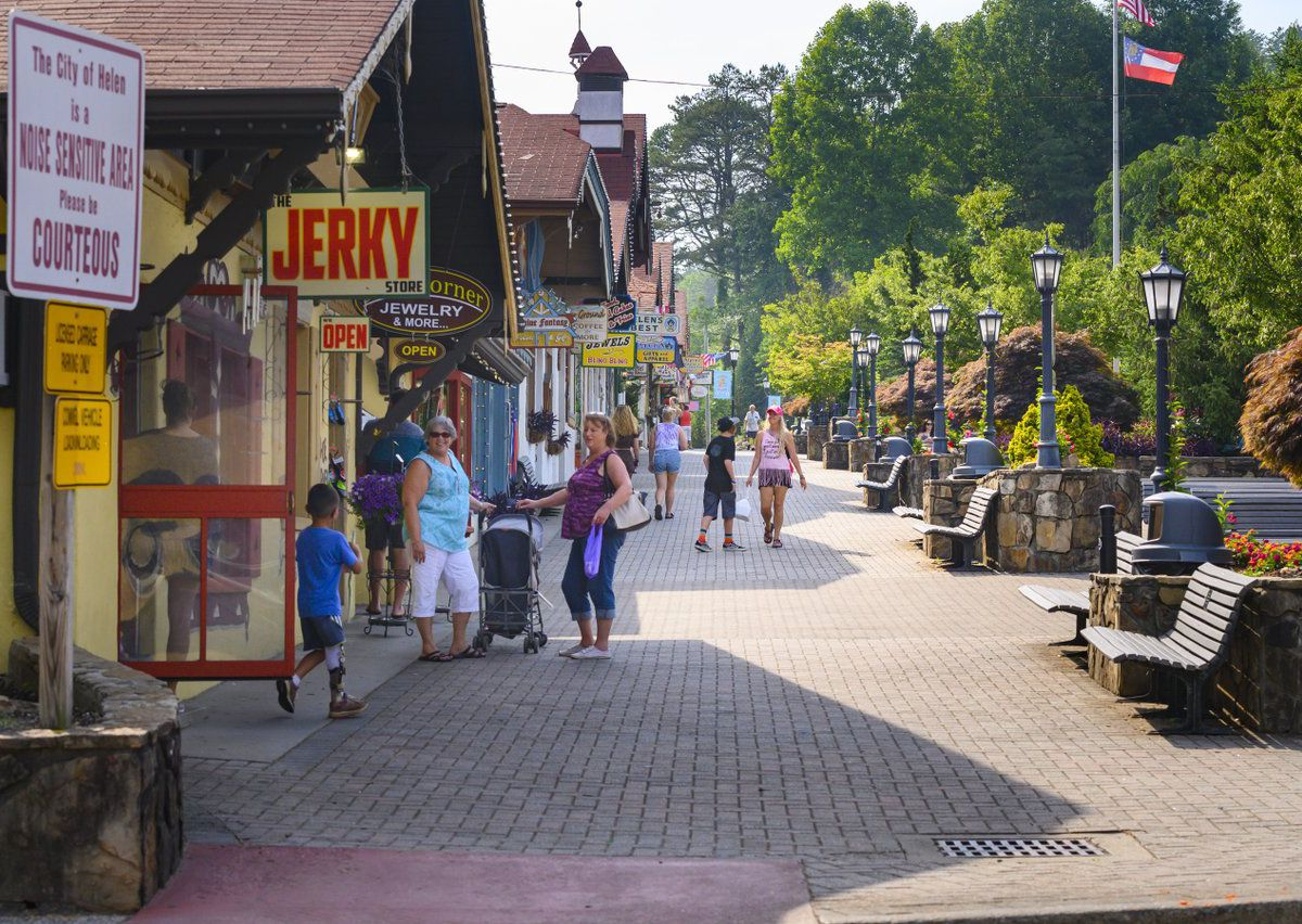 People walking along a sidewalk in front of shops on the left and flower beds on the right.