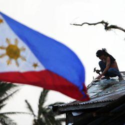 The Philippine flag flies as a man starts to rebuild in Tacloban, Thursday, Nov. 21, 2013.