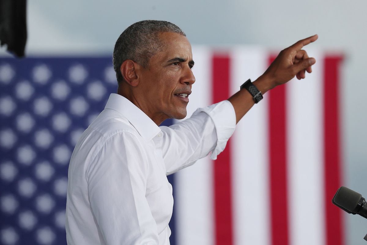 Obama speaks in profile against an American flag.