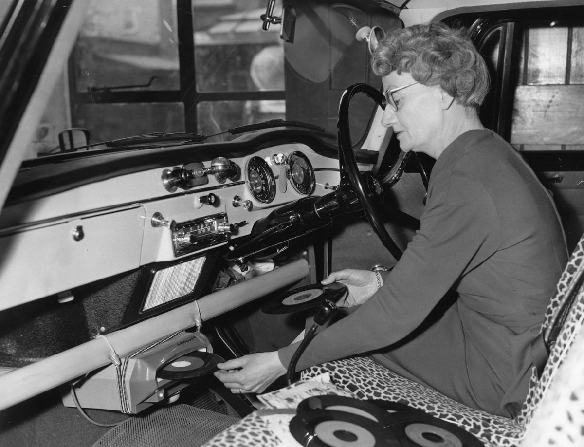 A woman uses her car record player.