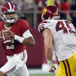 Alabama quarterback Jalen Hurts, left, looks to throw as Southern California defensive end Porter Gustin watches during the first half of an NCAA college football game Saturday, Sept. 3, 2016, in Arlington, Texas. (AP Photo/Tony Gutierrez)