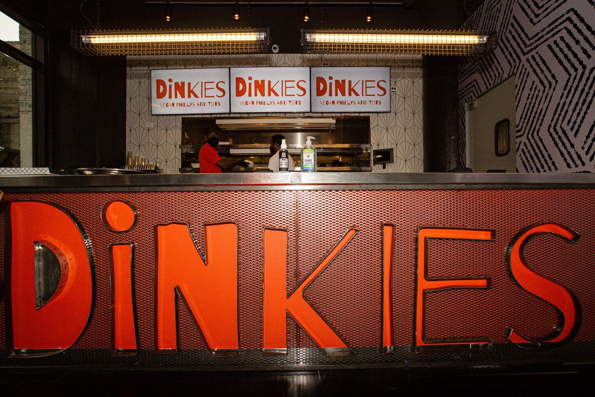 The red takeout stall and kitchen of Dinkie's inside Bar Vegan at Ponce City Market with two masked workers standing beneath three lit up red and white Dinkies logo signs