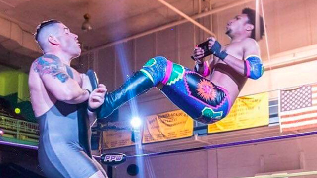 A wrestler performs a dropkick while glued to his gaming device.