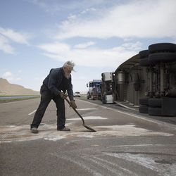 Bob Williams and Kenny Phillips clean the road after a semitrailer was toppled by the wind on I-80 near Dugway on Monday, June 12, 2017.