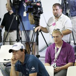 Rory McIlroy of Northern Ireland, bottom left, listens to Tiger Woods at a news conference during the Pro-Am of the BMW Championship PGA golf tournament at Crooked Stick Golf Club in Carmel, Ind., Wednesday, Sept. 5, 2012.