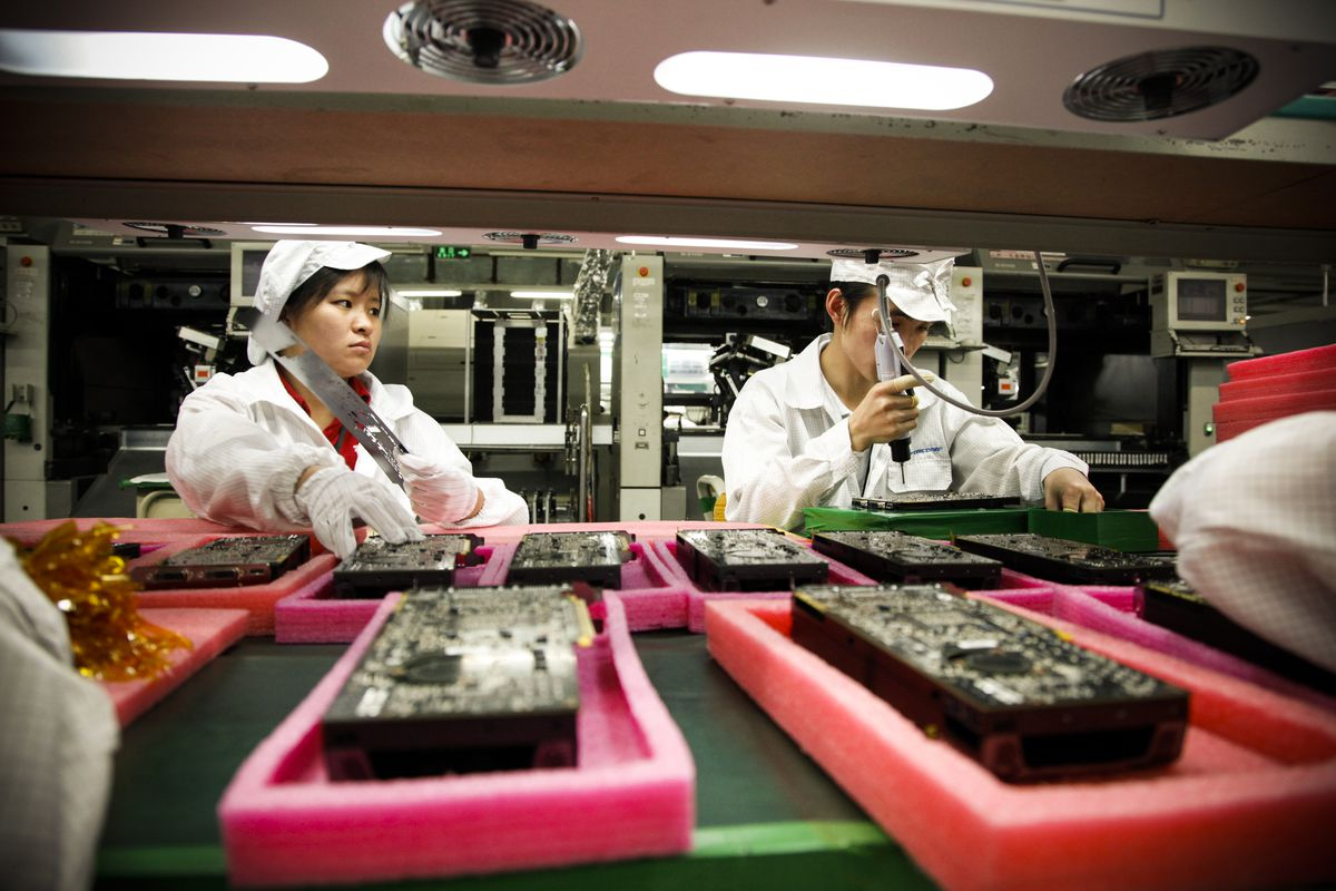 Employees work on the assembly line at Hon Hai Group's Foxconn plant in Shenzhen, China, on Wednesday, May 26, 2010. Hon Hai is the parts supplier for many high-tech companies around the world including Apple Inc., Hewlett-Packard Co., and Dell Inc.
