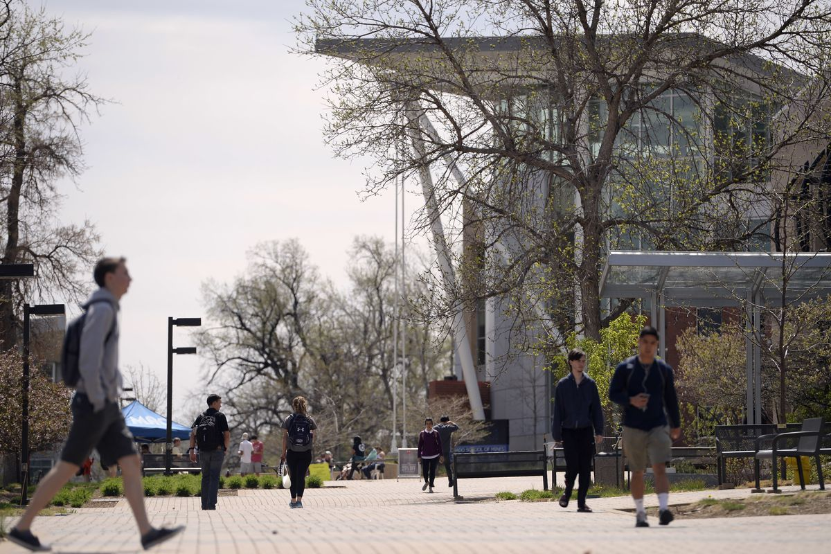 Students walk through a Colorado college campus, a large building with a flat roof looming in the background down the walkway.