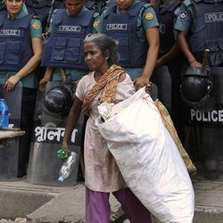 A Bangladeshi rag picker woman walks past Bangladeshi police officers standing guard during a nationwide general strike in Dhaka, Bangladesh, Sunday, April 29  2012. Schools and businesses have remained closed in Bangladesh's capital, Dhaka, as an 18-party opposition alliance has enforced a daylong nationwide general strike to demand the government find a leader who went missing nearly two weeks ago.