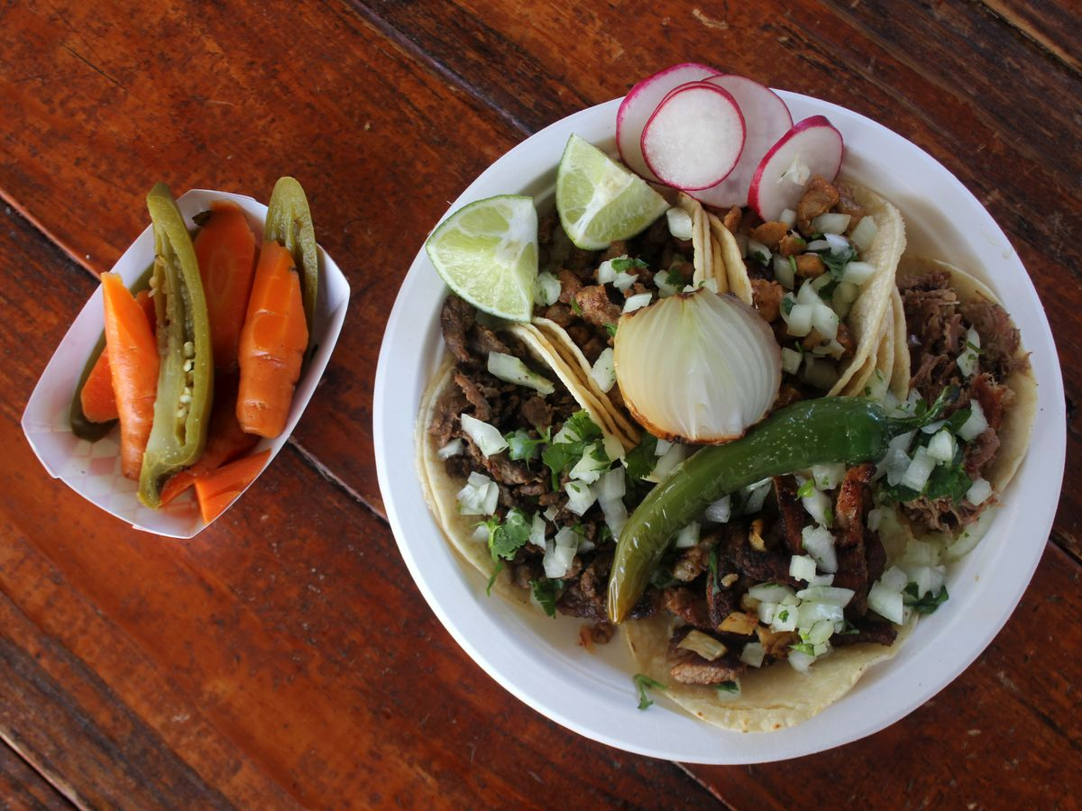 A bird's eye view of a taco platter, with radishes, limes, and a side of pickled vegetables.