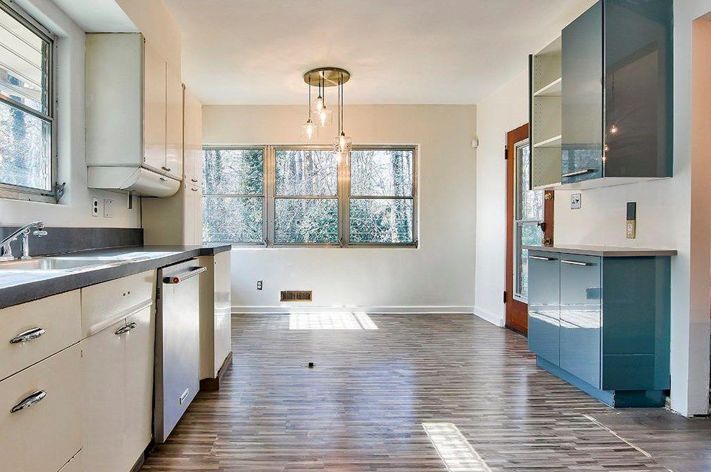 An old kitchen with modern cabinets.
