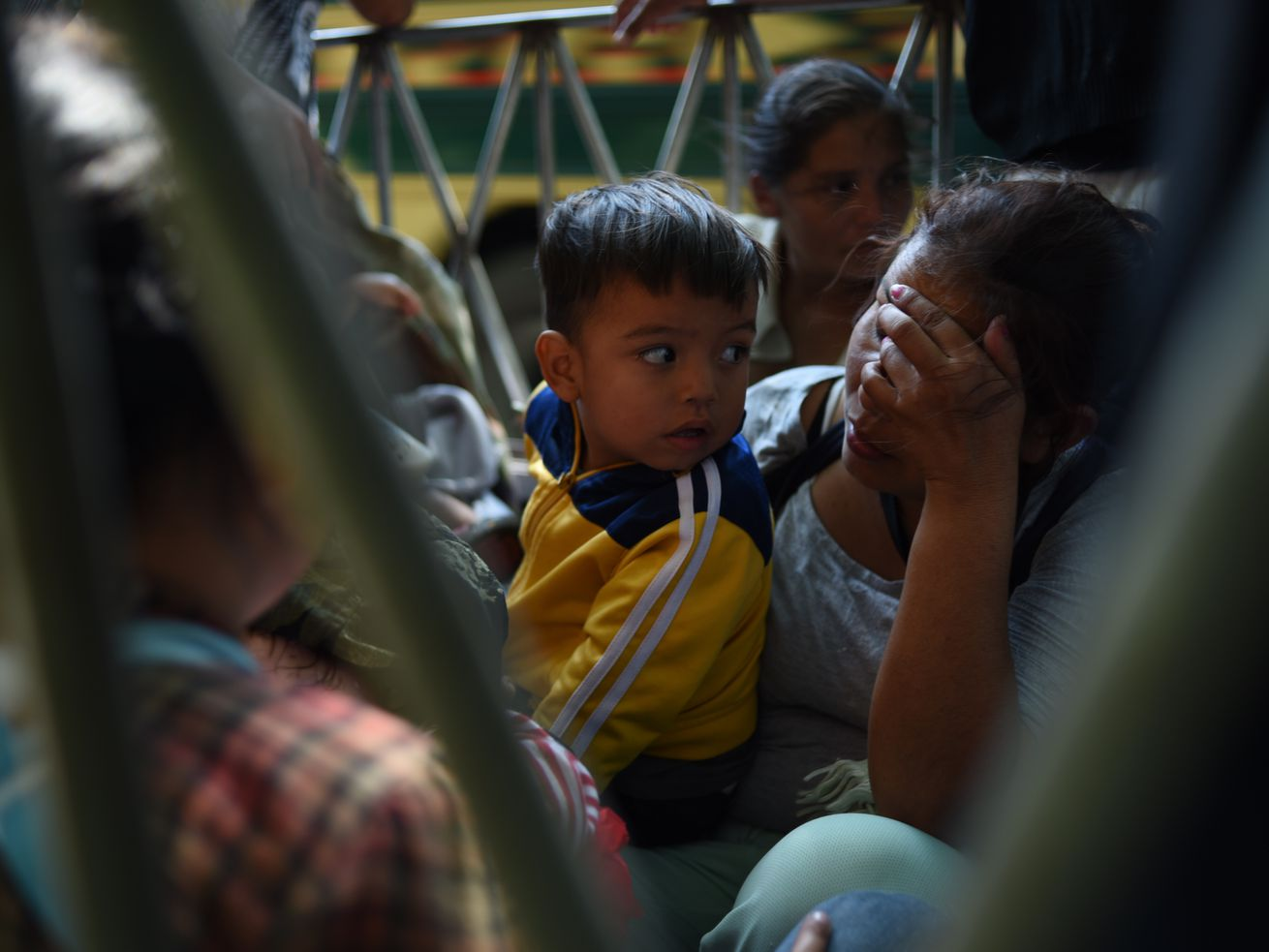 A woman with her face in her hand holds onto her young son as they travel to the United States from Honduras.