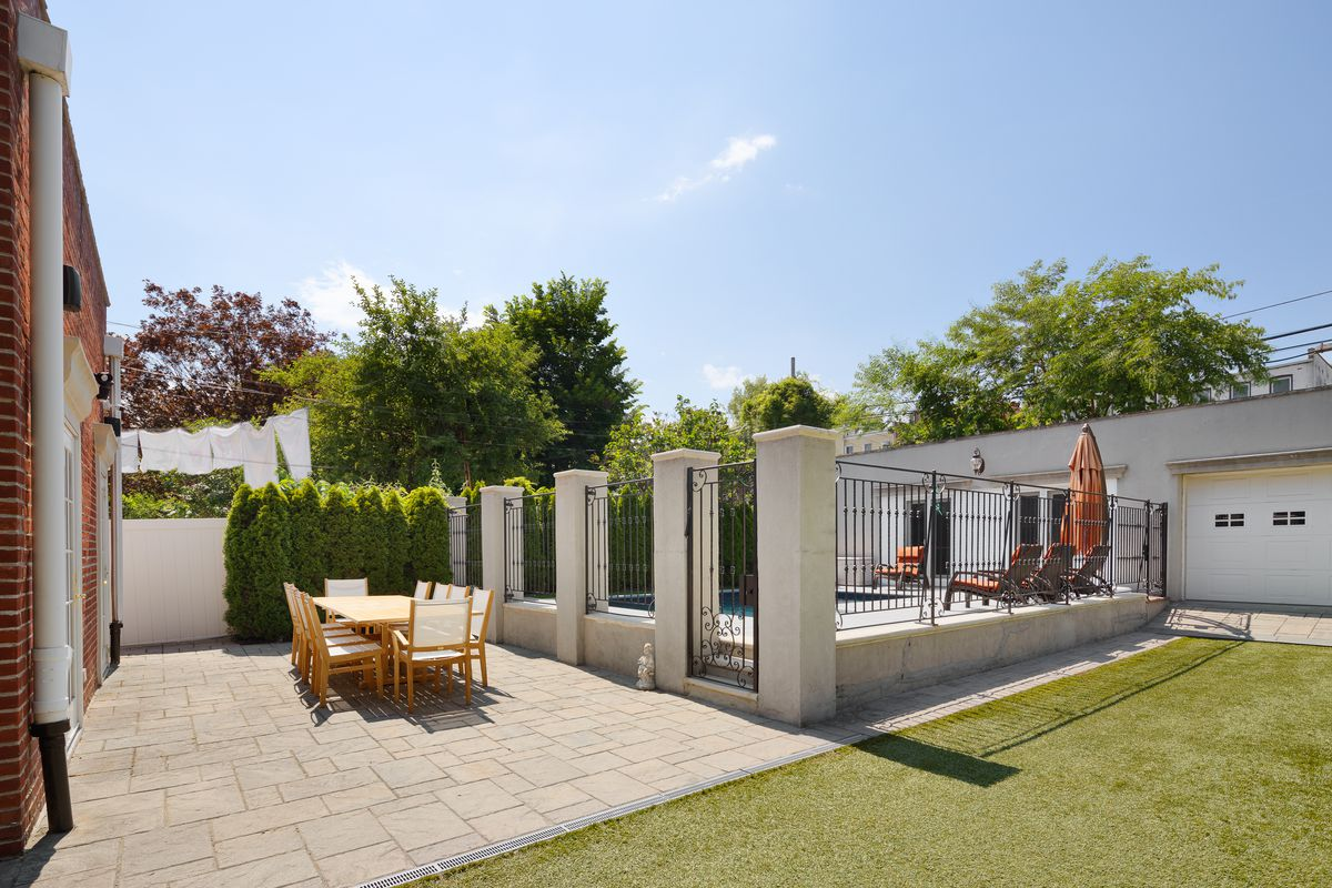 A backyard with a fenced in-ground pool, a table with several chairs, and a synthetic turf.