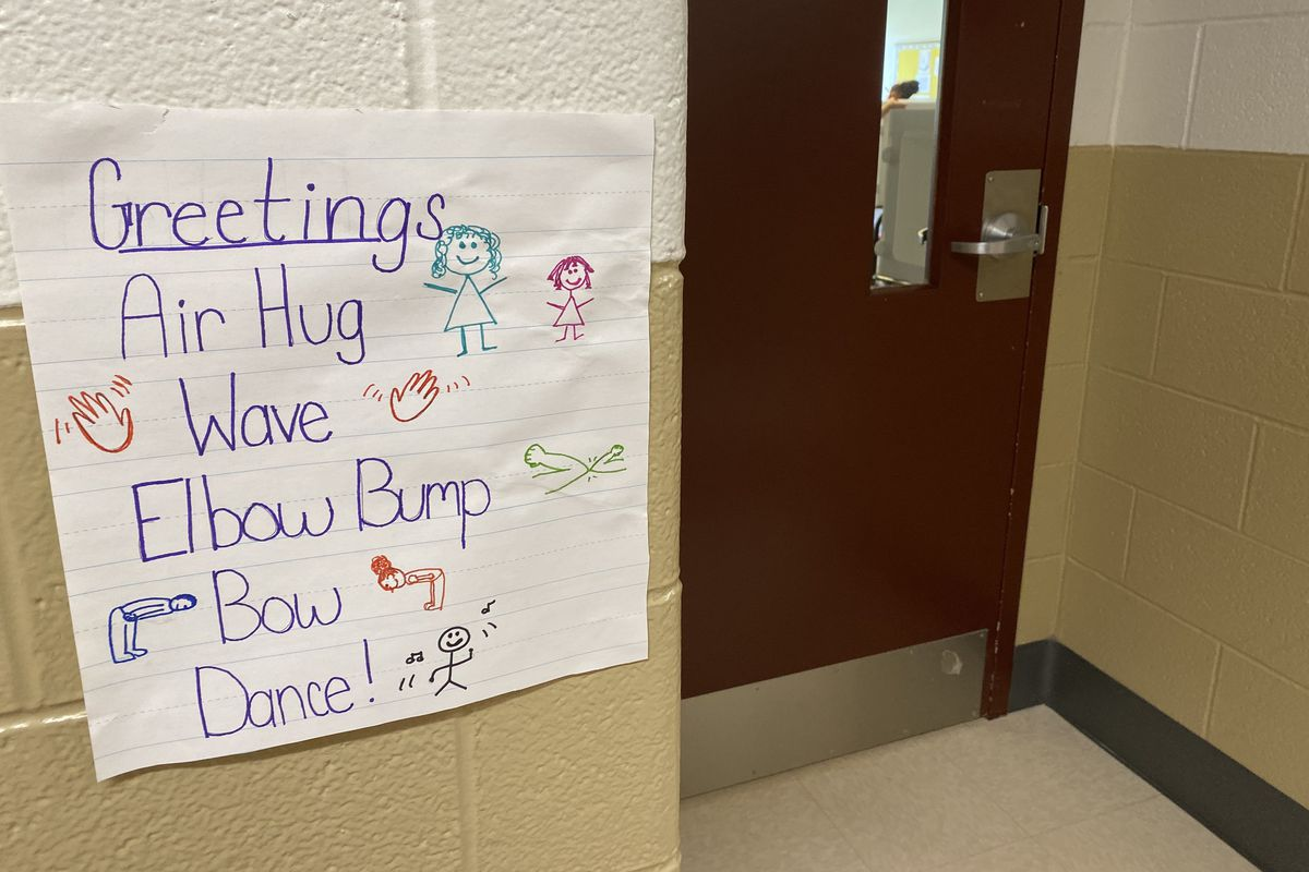 """A sign in a hallway by a door at Tindley Summit Academy in Indianapolis says """"Air hug, wave, elbow bump, bow, dance"""""""