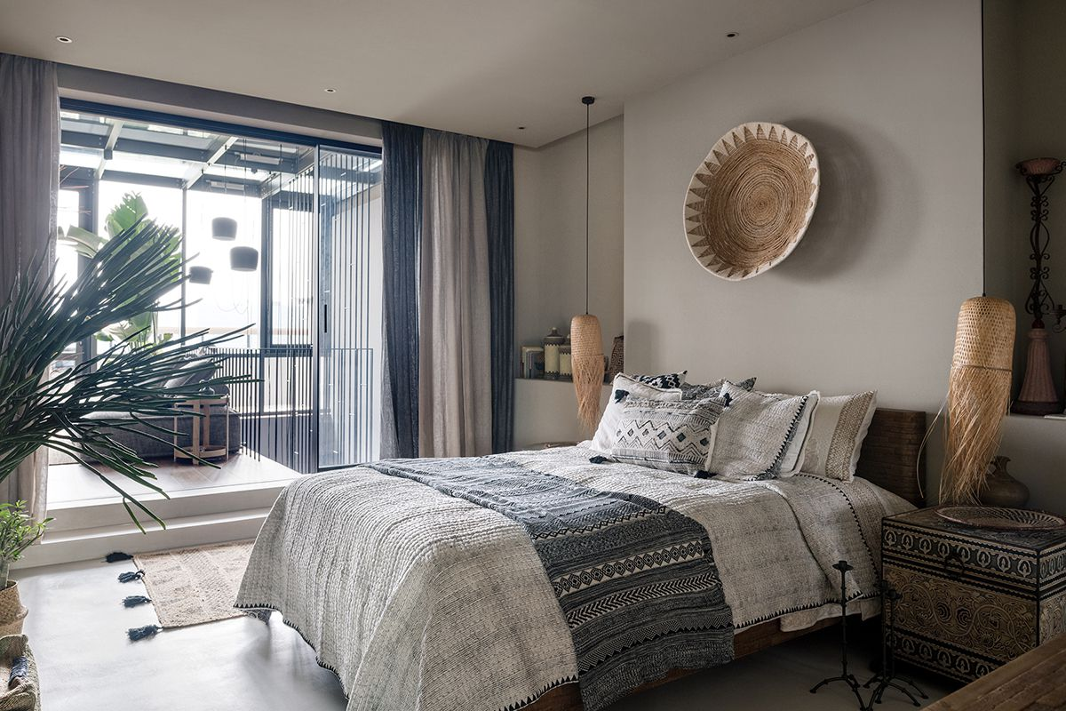 A bedroom swatched in natural tones, including woven wall decor, boho-style bedding, and gray curtains.
