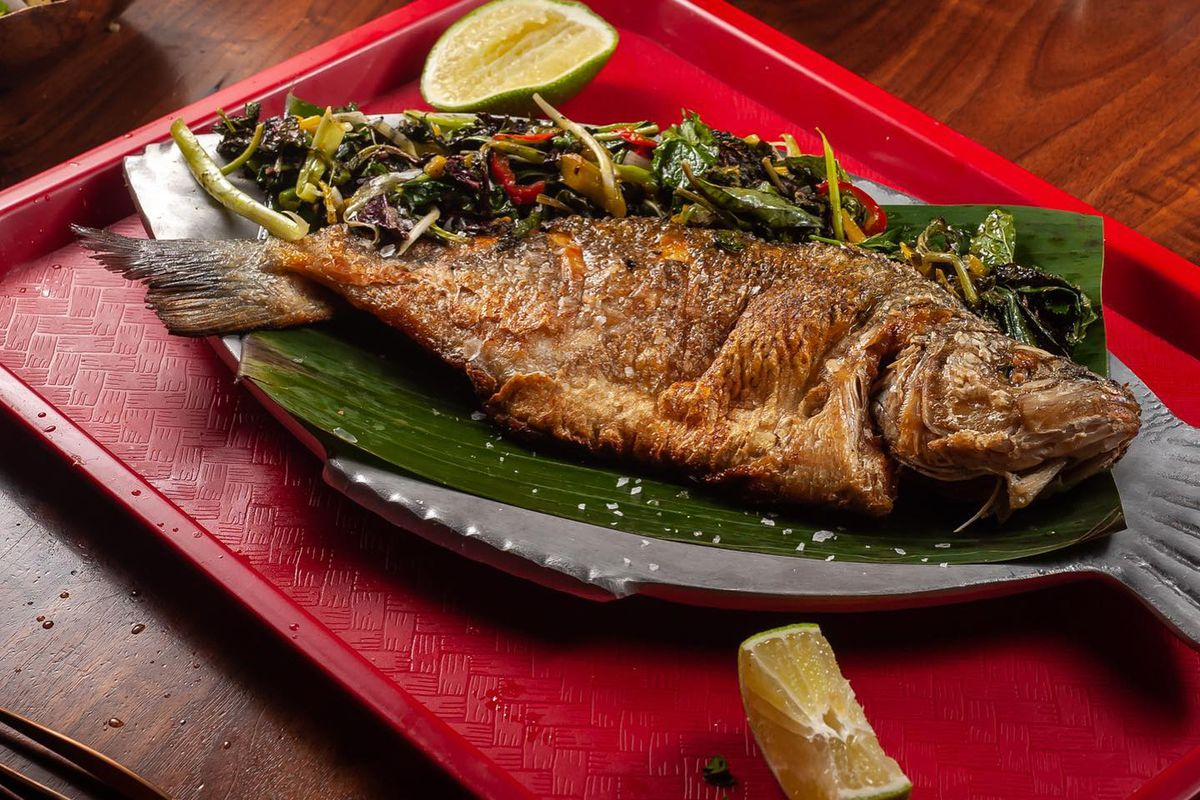 A whole roasted fish on a banana leaf with pickled garnish and a lime
