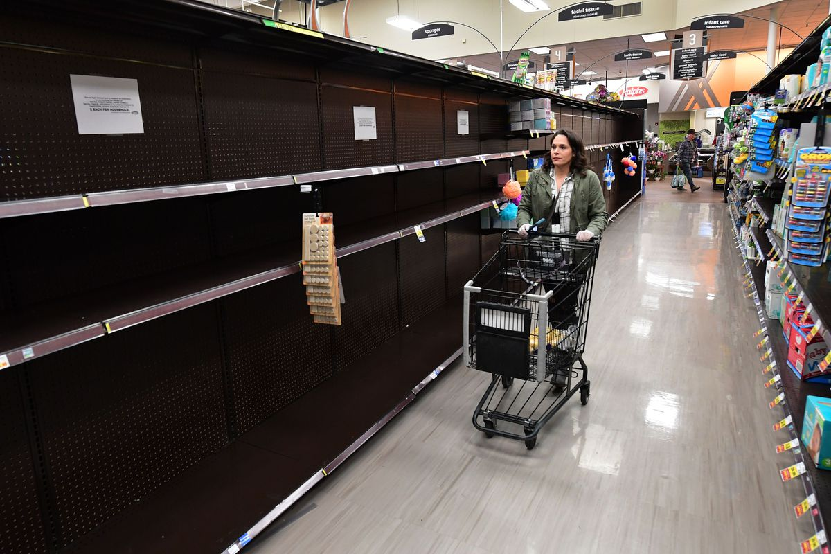 An Instacart employee pushes a cart down an aisle with empty shelves in North Hollywood, California, on March 19, 2020.