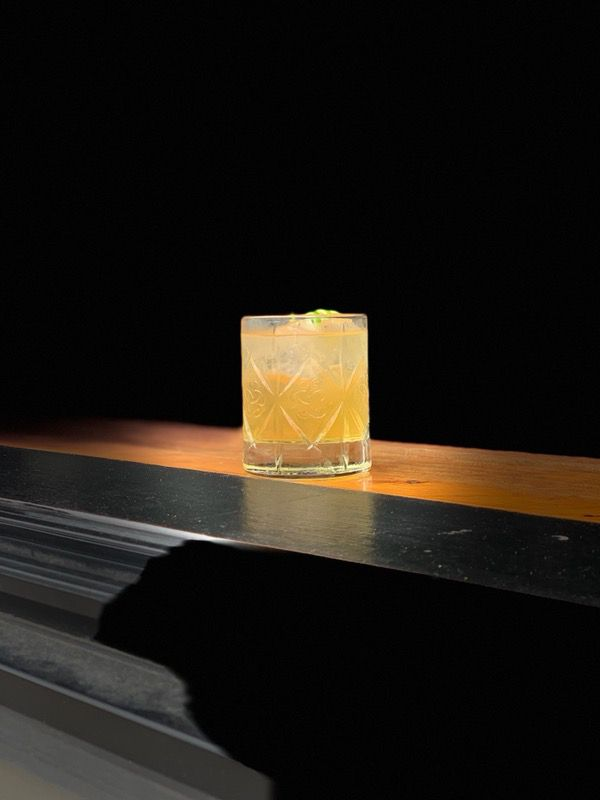 A rocks glass filled with a yellow drink.