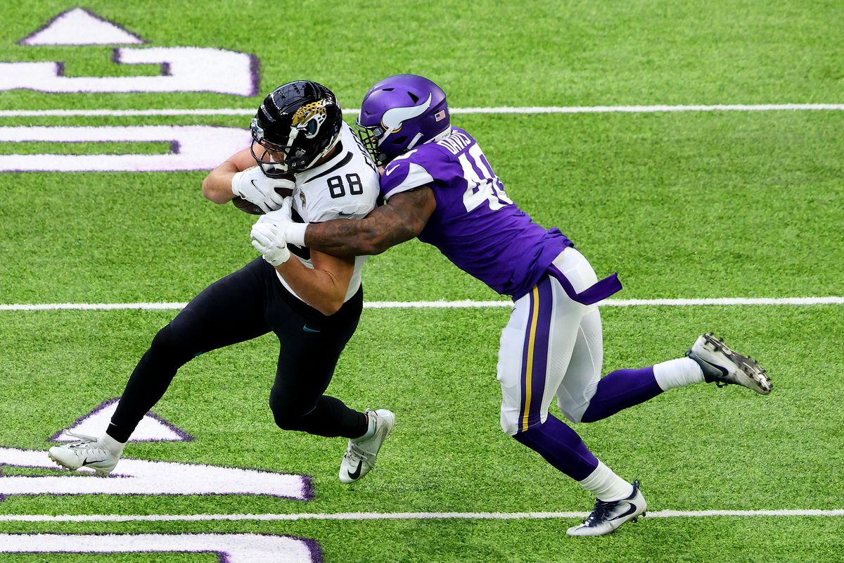 Tyler Eifert #88 of the Jacksonville Jaguars gets the first down with this run as Todd Davis #40 of the Minnesota Vikings makes the tackle in the first quarter at U.S. Bank Stadium on December 06, 2020 in Minneapolis, Minnesota.