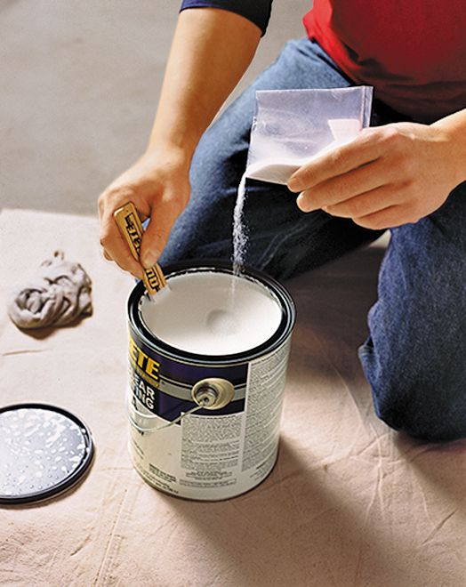 Person pouring hardener to create top coat while to prepare for the final step in the process of applying epoxy to a garage floor.