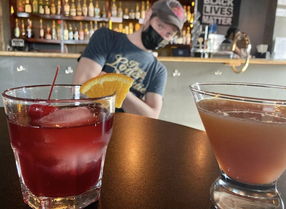 Two cocktails (one red, one peach) in the foreground, with a masked man wearing a baseball cap leaning to the side in the background.