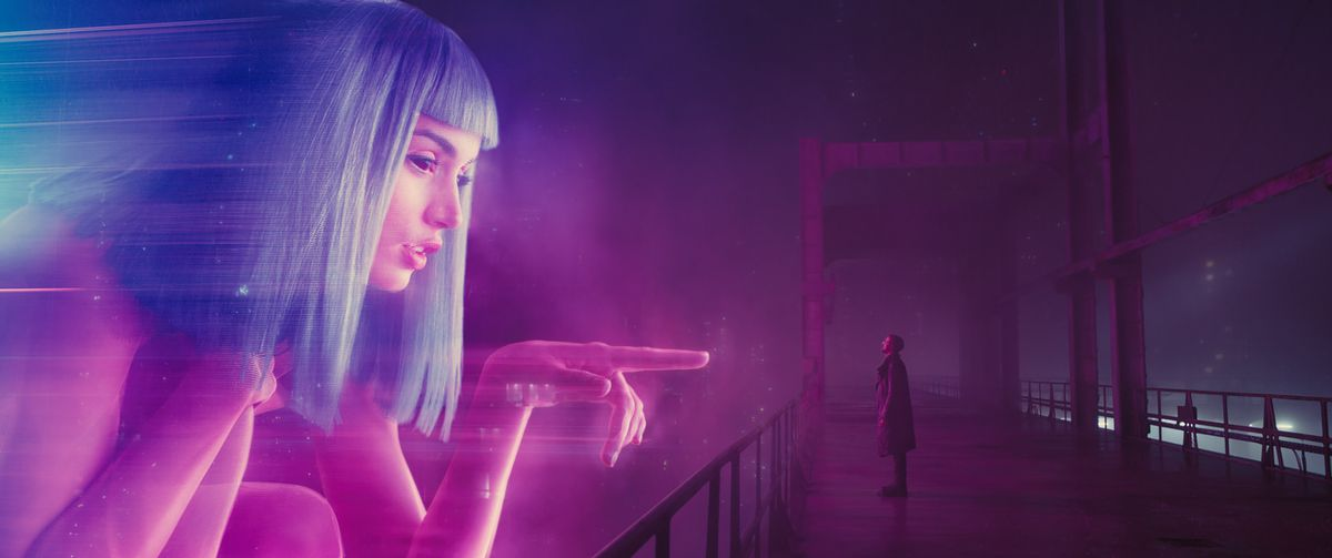 Ryan Gosling standing in front of a hologram in Blade Runner 2049.
